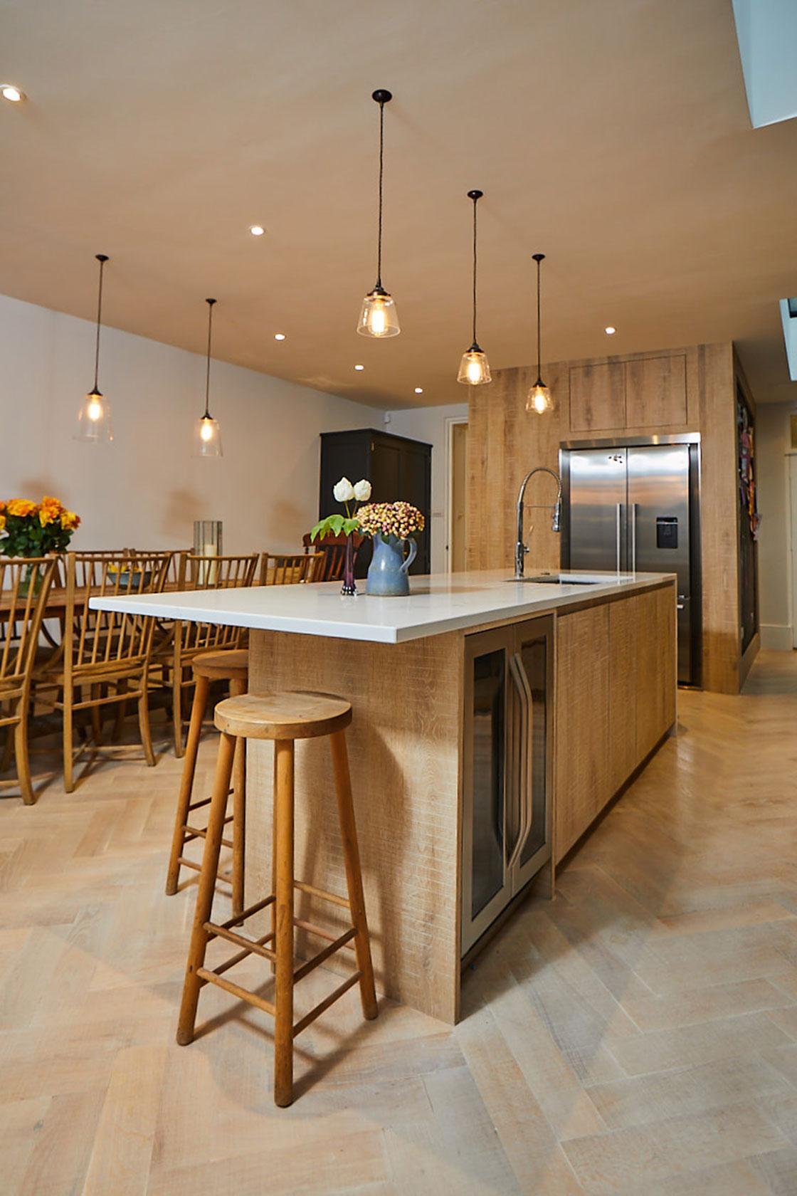 Oak breakfast bar stool sits under white Caesarstone worktop