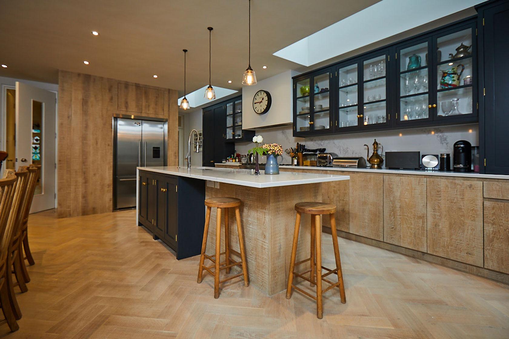Kitchen island and bespoke range run with parquet wood floor boards