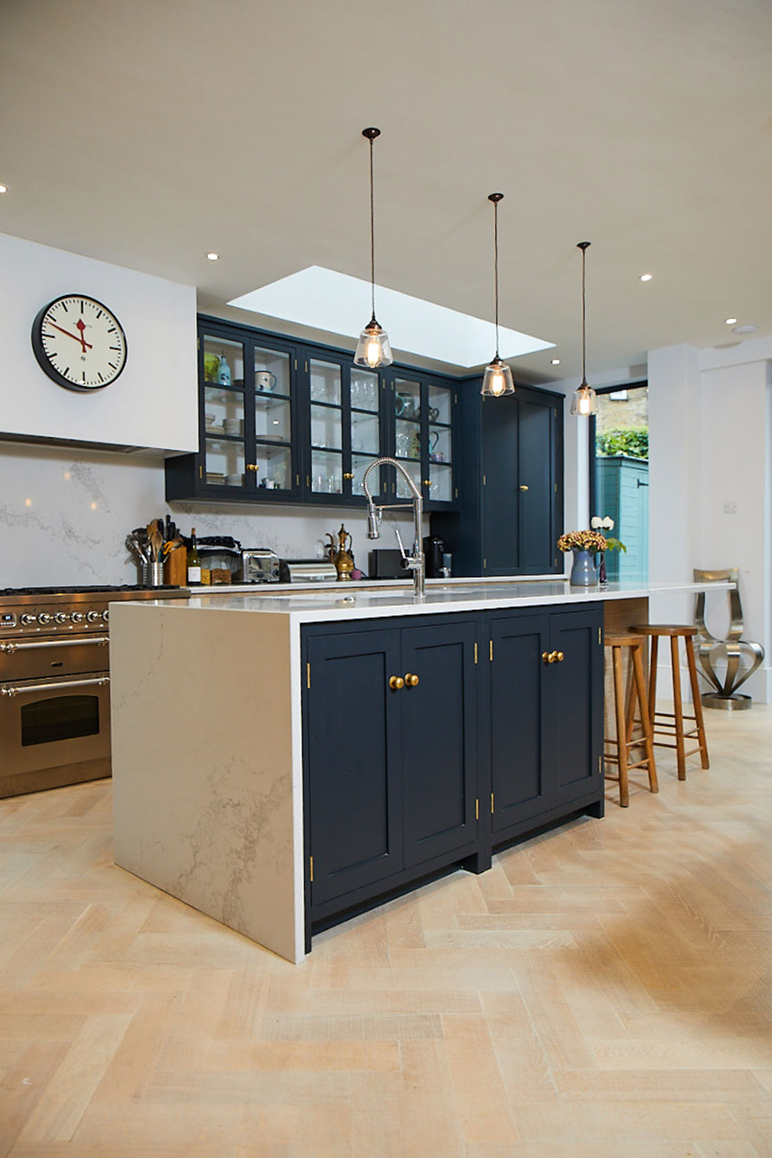 Dark blue double doors on kitchen island with white caesartone worktop and parquet wood floor