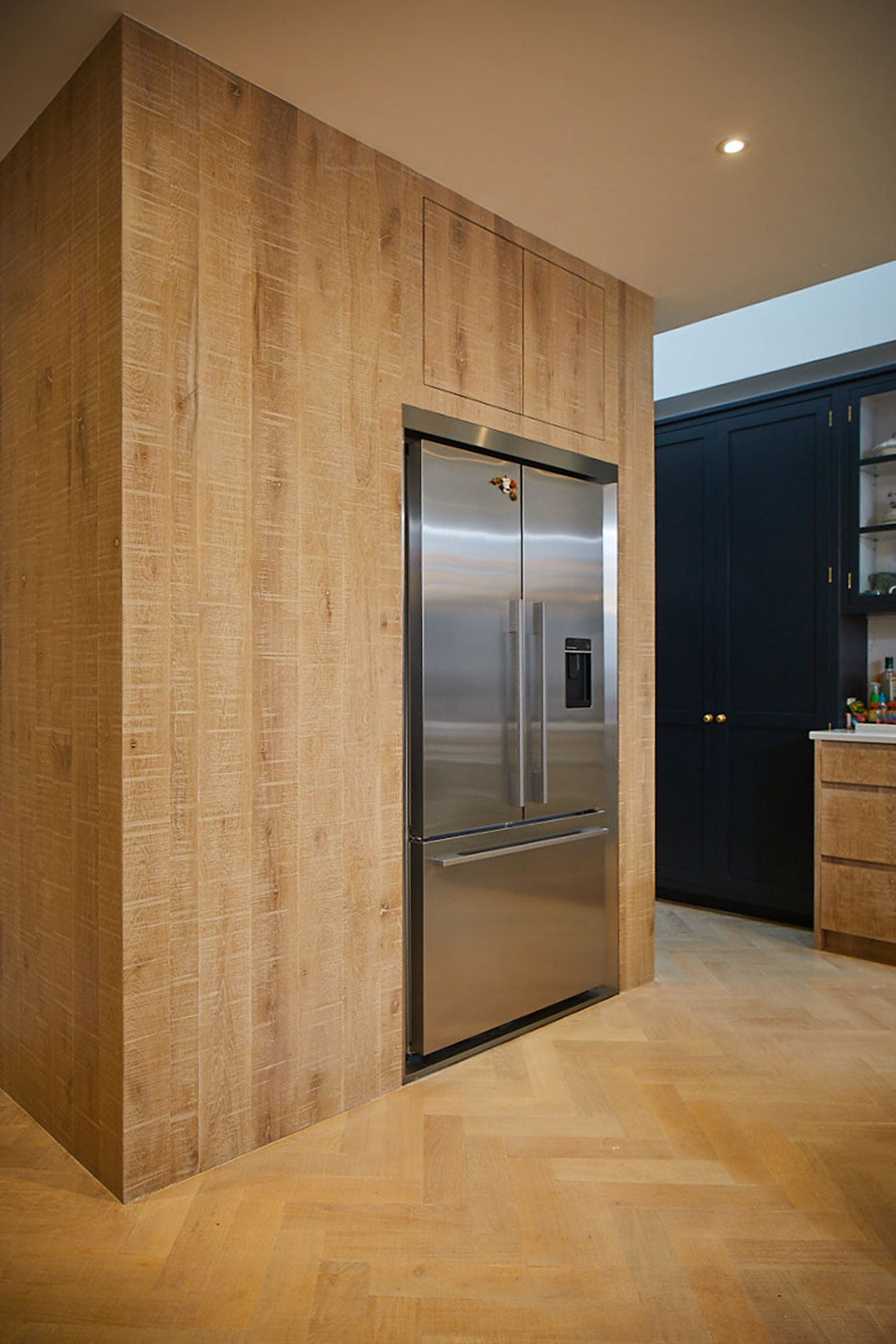American stainless fridge freezer integrated in to white washed oak kitchen cabinets