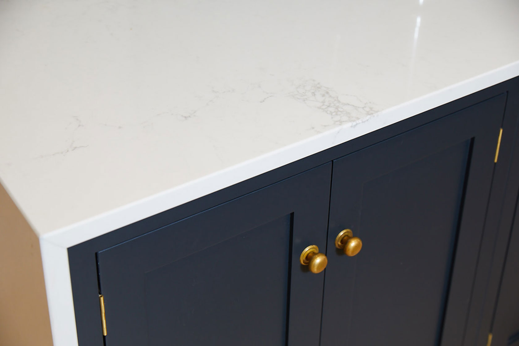 Caesarstone worktop sits on bespoke shaker cabinets with burnt brass knobs