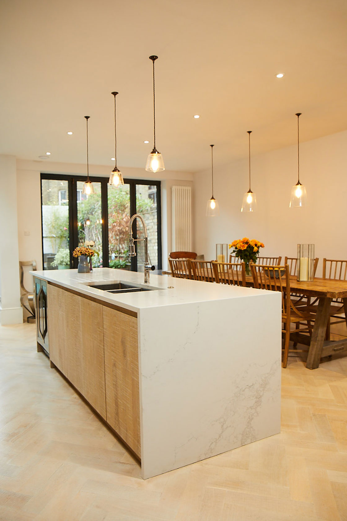 Limed oak engineered slab cabinet doors on kitchen island with quartz Caesarstone white worktop