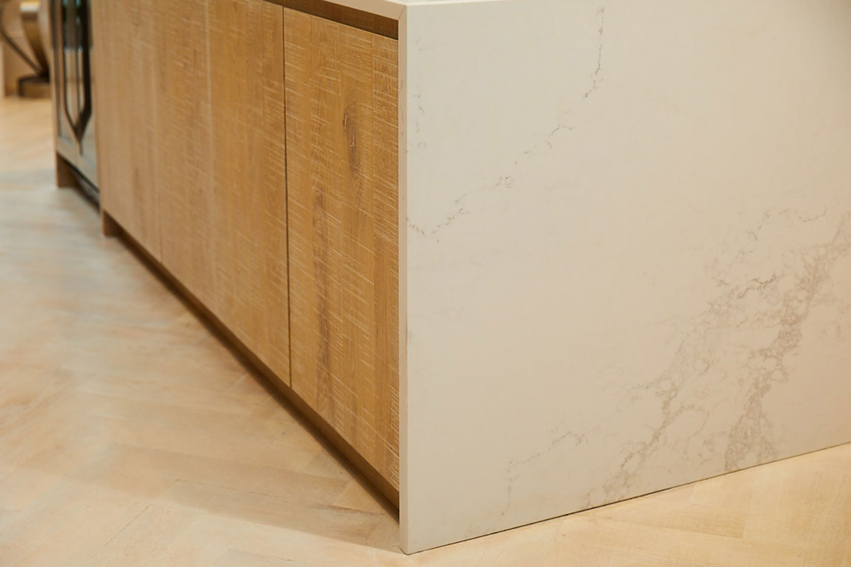 Slab oak kitchen cabinets sit on oak wood parquet flooring