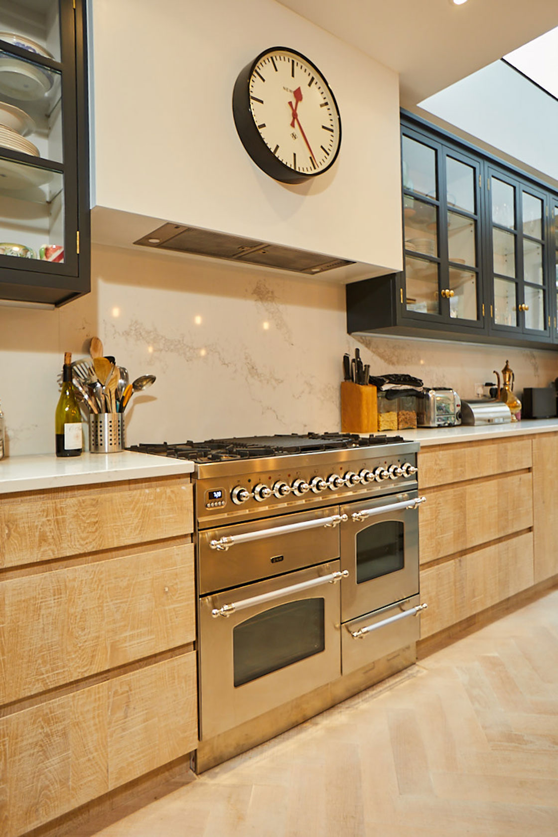 Stainless steel range cooker sits in between limed oak kitchen cabinets with floating minimal white canopy