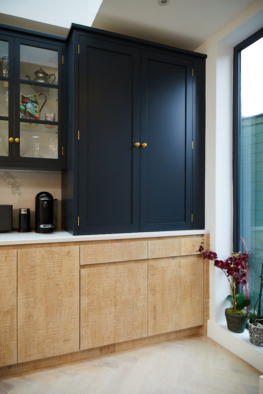 Dark blue shaker wall cabinets sit on Caesarstone worktop with limed oak slab base units below
