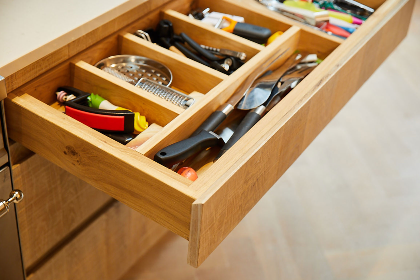 Solid oak drawer divide filled with knives and utensils