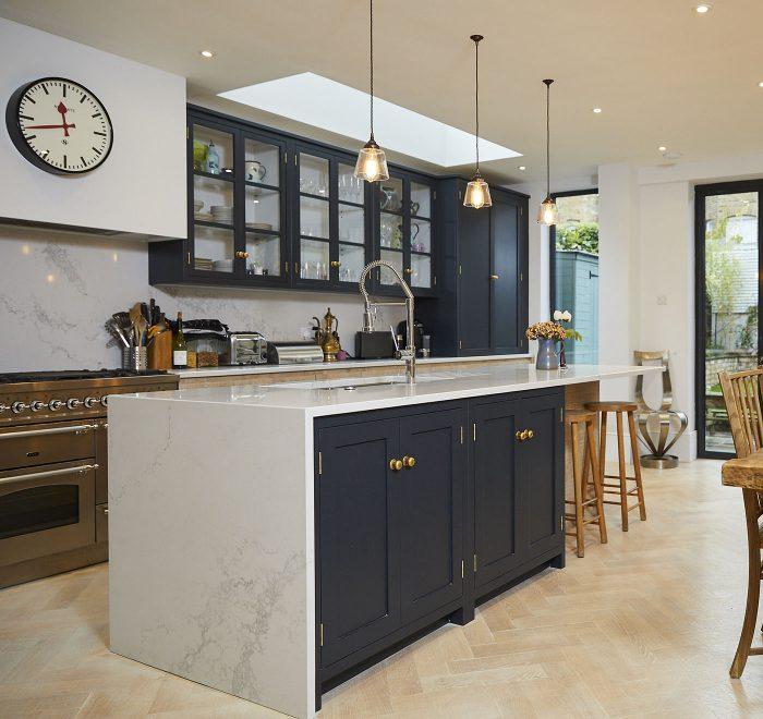 White quartz waterfall worktop on dark blue kitchen units with brass knobs
