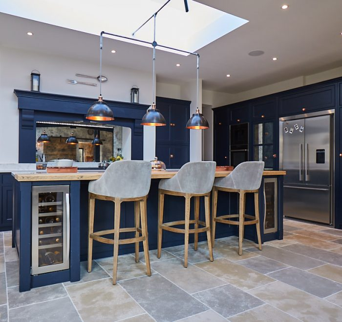 Upholstered bar stools sit under bespoke dark blue kitchen island