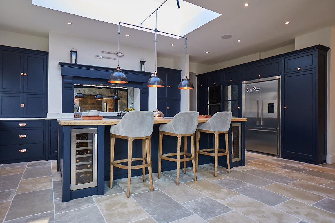 Upholstered bar stools sit under bespoke dark blue kitchen island