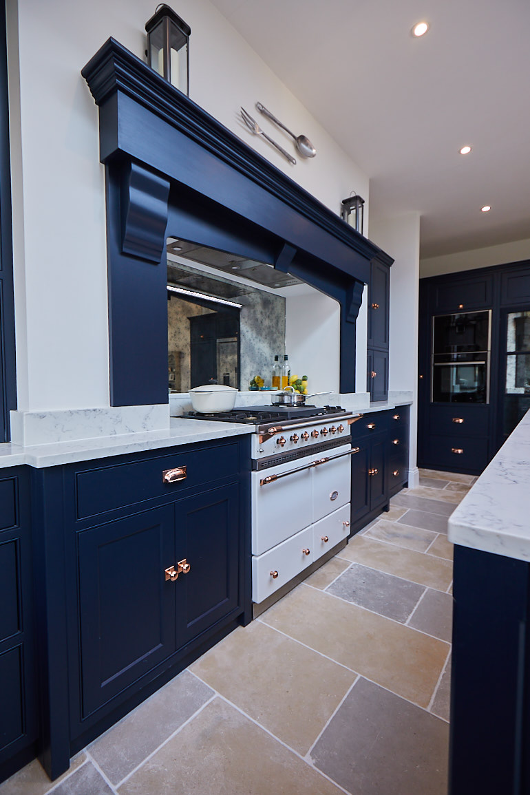 White Macon range cooker by lacanche with dark blue mantle on false chimney breast