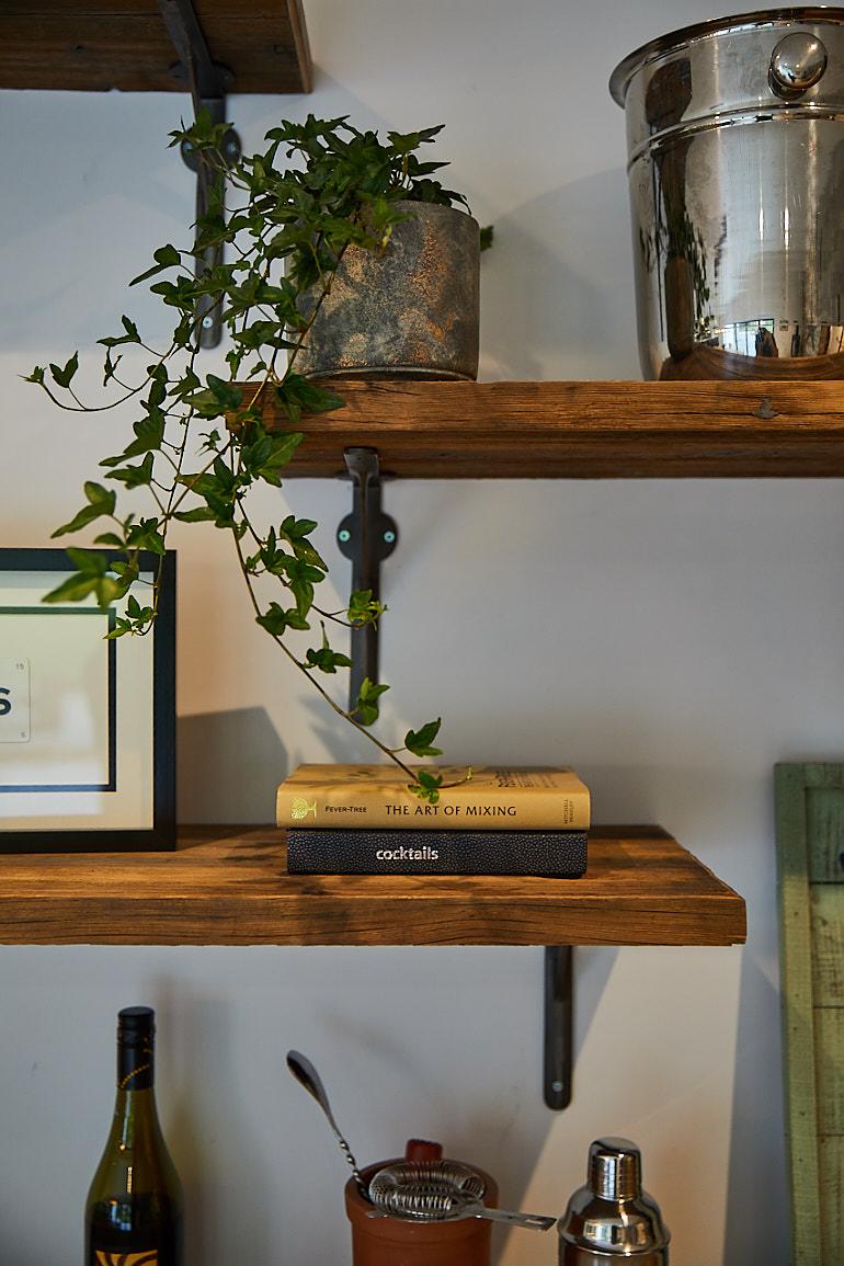 Plants sit on reclaimed shelves on cast brackets
