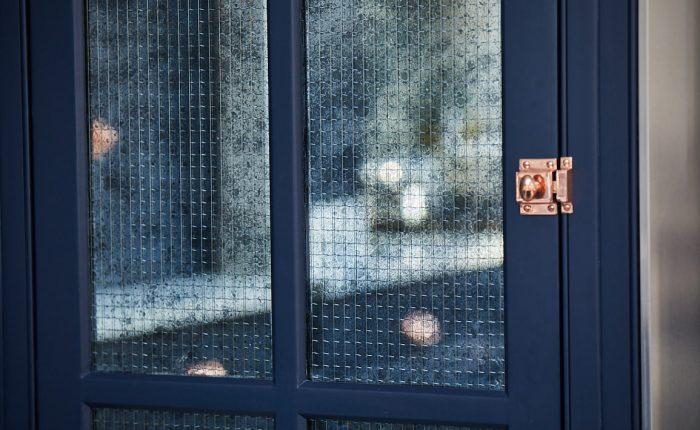 Mirror with wirework reflects dark blue kitchen