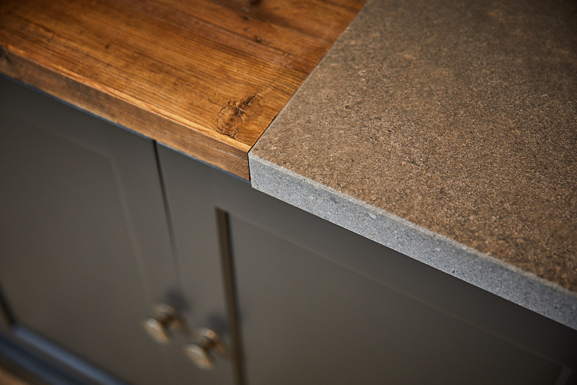 Reclaimed pine and grey Caesarstone worktops sit on kitchen cabinets