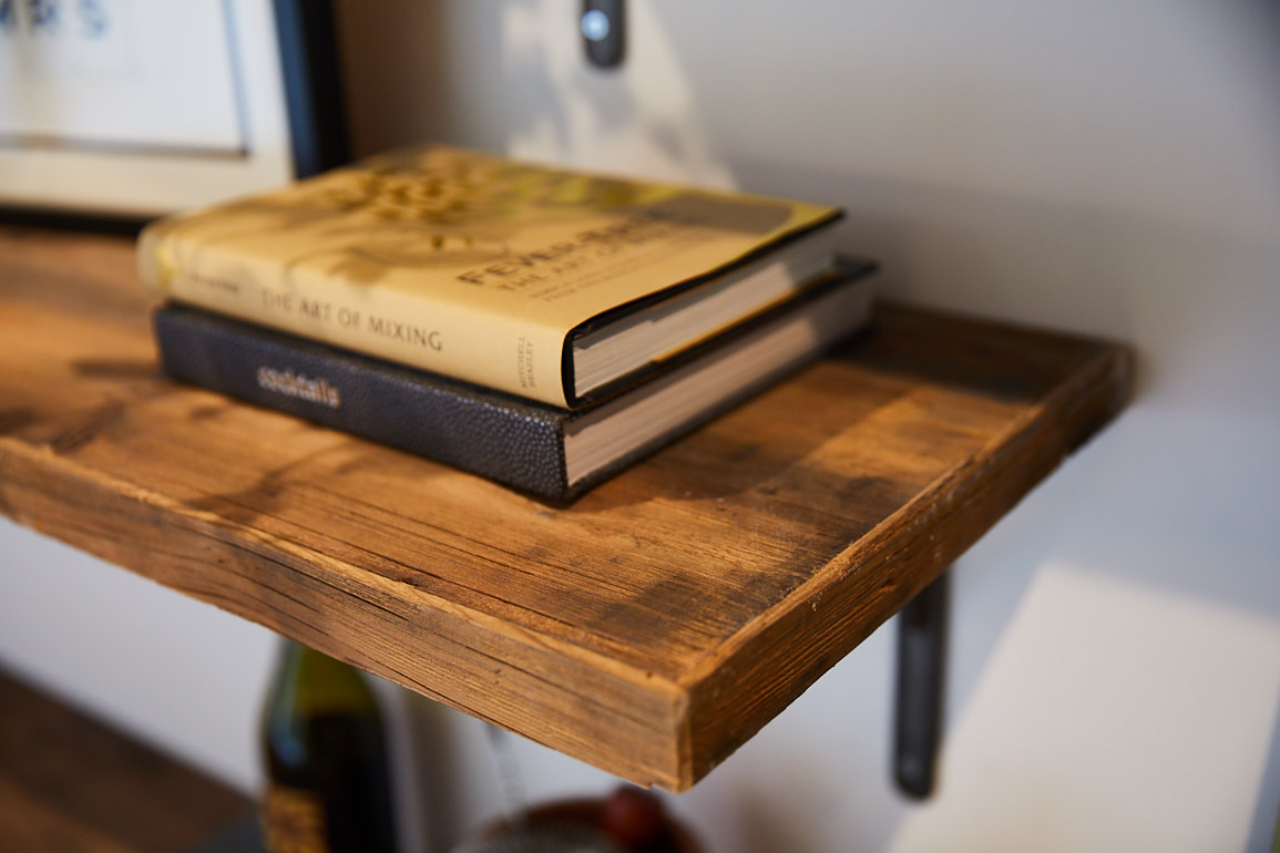 Books rest on reclaimed rustic pine shelf with cast iron bracket