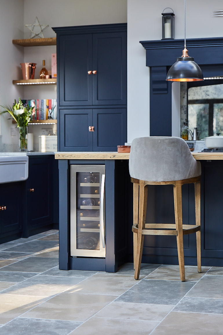 Wine cooler in kitchen island with two painted chunky posts in dark blue