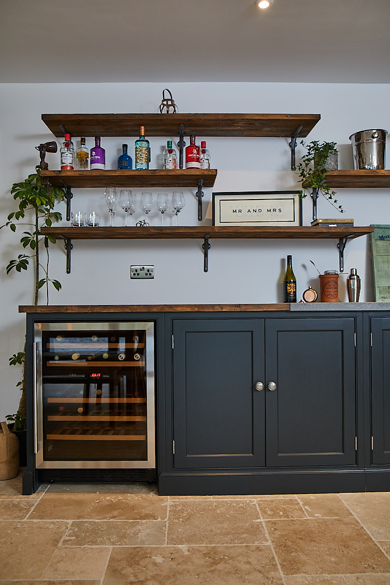 Wine cooler sits below open rustic shelves with plants and books