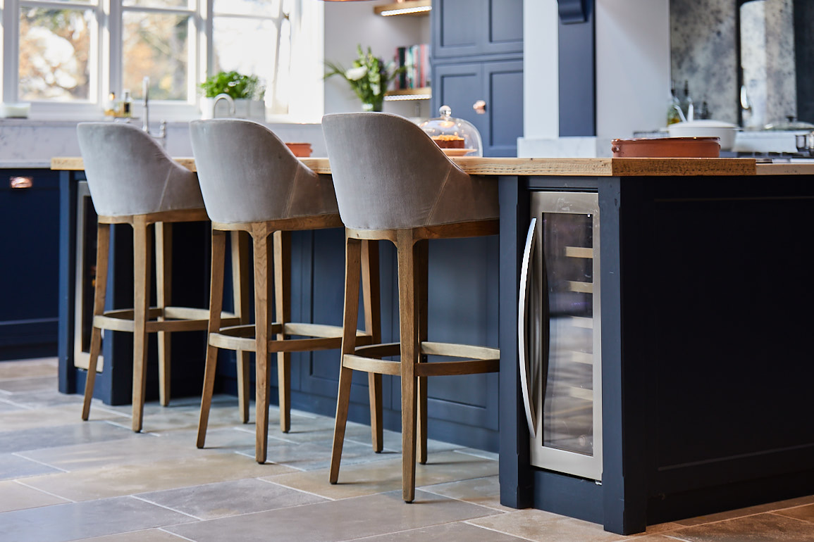 300mm wine cooler semi integrated in to dark blue kitchen island next to bar stools