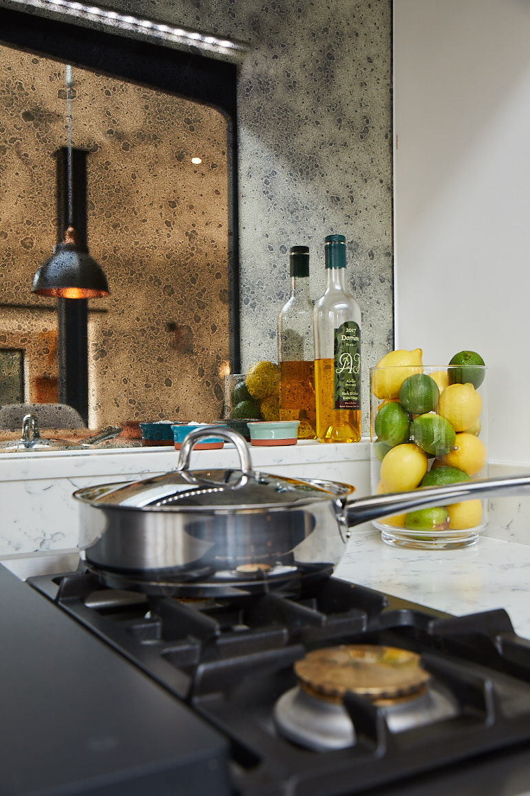 Vintage mirror reflects lemon and limes on gas hob