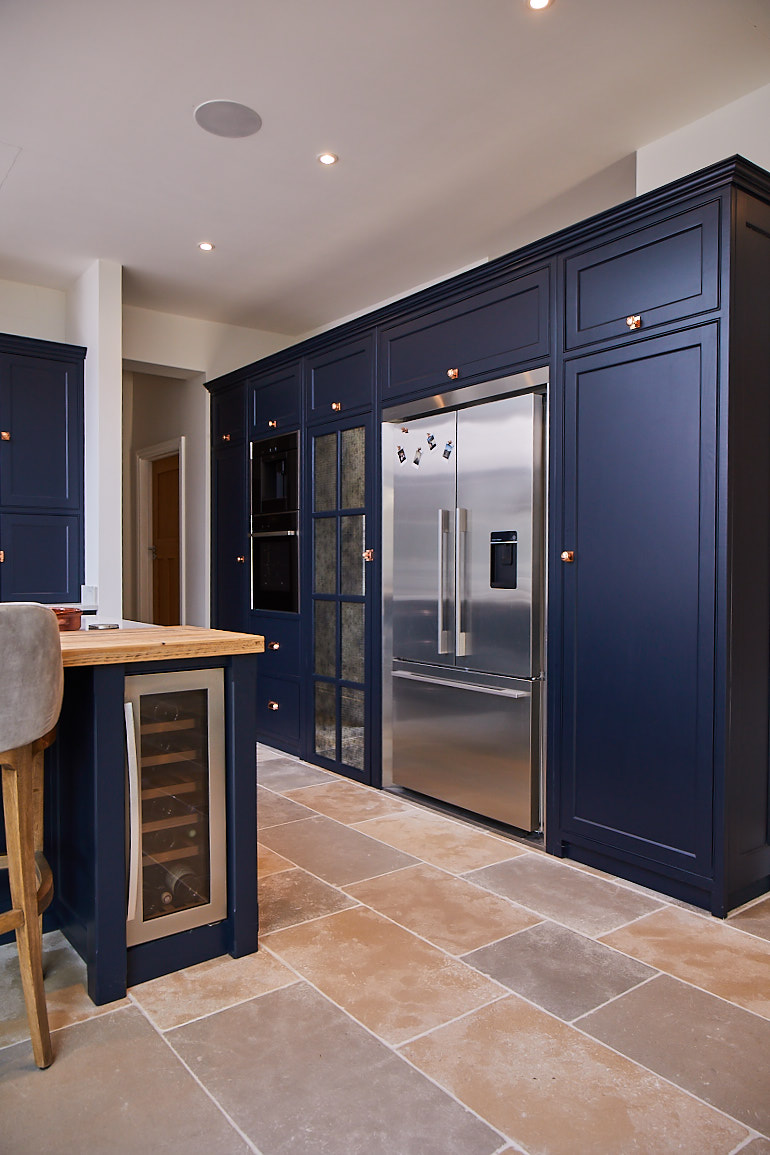 Fisher & Paykel American fridge freezer with surround kit integrated in to large dark blue kitchen cabinets