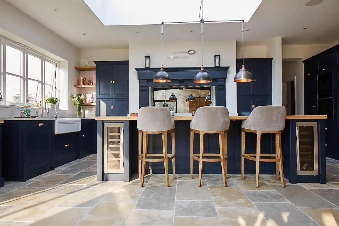 Upholstered bar stools under bespoke kitchen island by The Main Company