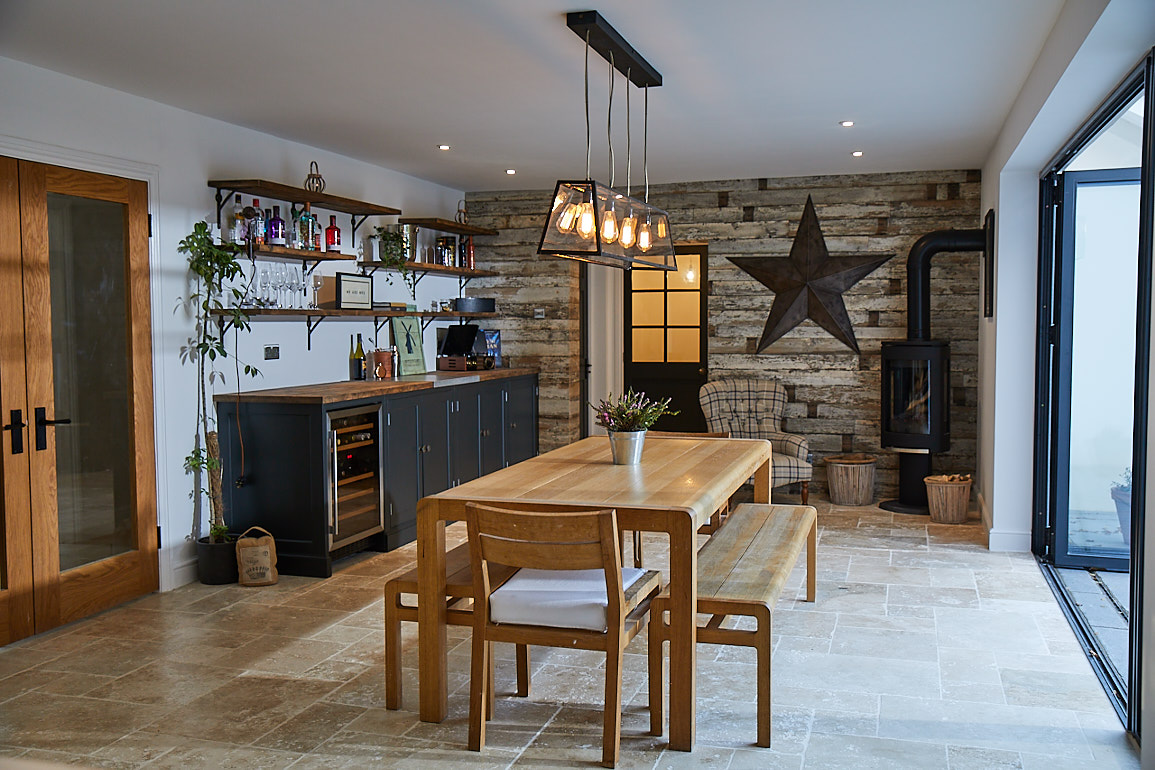 Oak dining table and bench sits in open plan kitchen with cladded wood wall