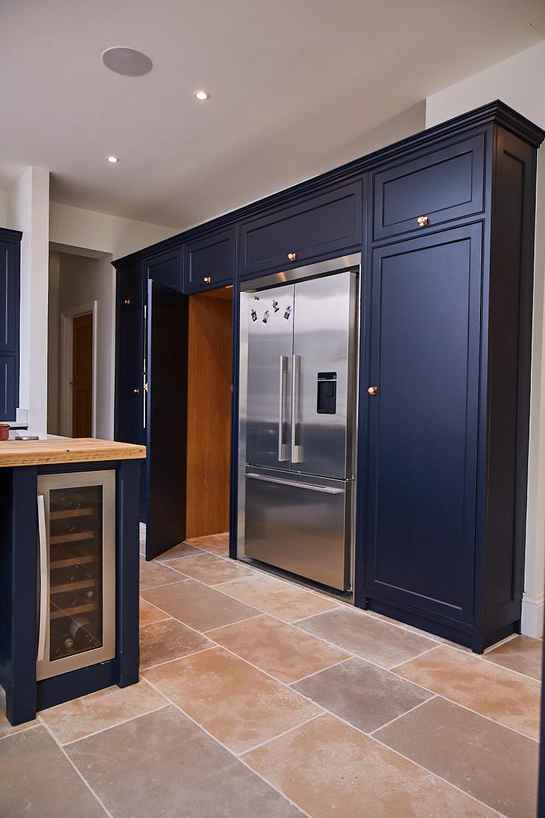 Secret pantry door to look like kitchen cabinet painted in dark blue