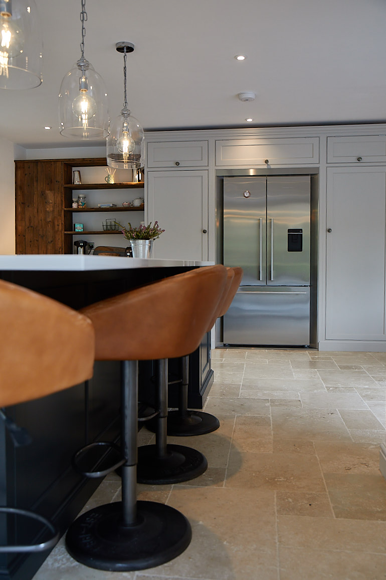 Light leather bar stools sit in front of Fisher & Paykel American fridge freezer integrated in painted kitchen units