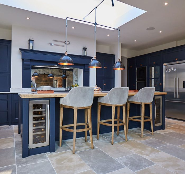 Blue kitchen island with integrated wine cooler and three black pendant lights