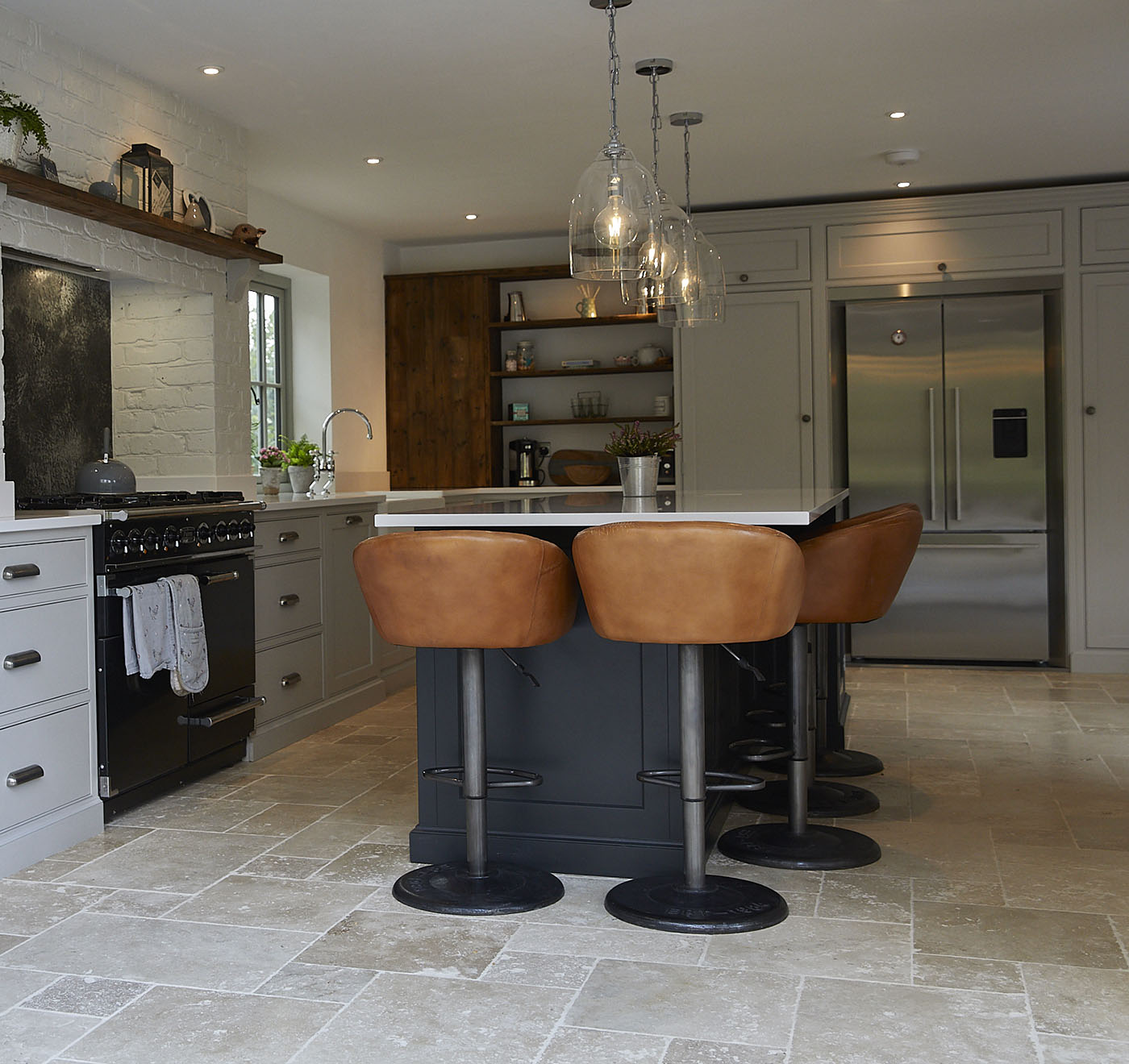 Brown leather barstools under kitchen island next to black Lacanche range cooker
