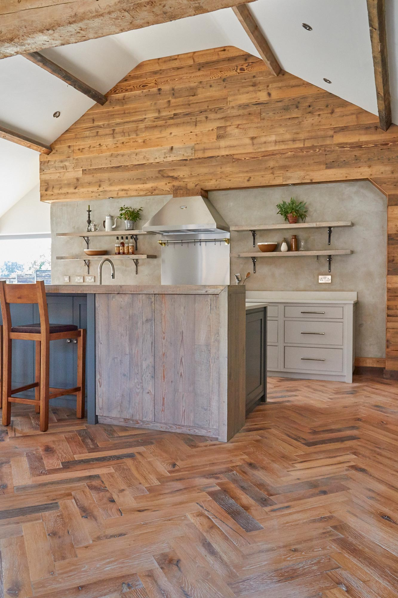 Bespoke island with reclaimed slab cabinet doors sits on herringbone wood floor