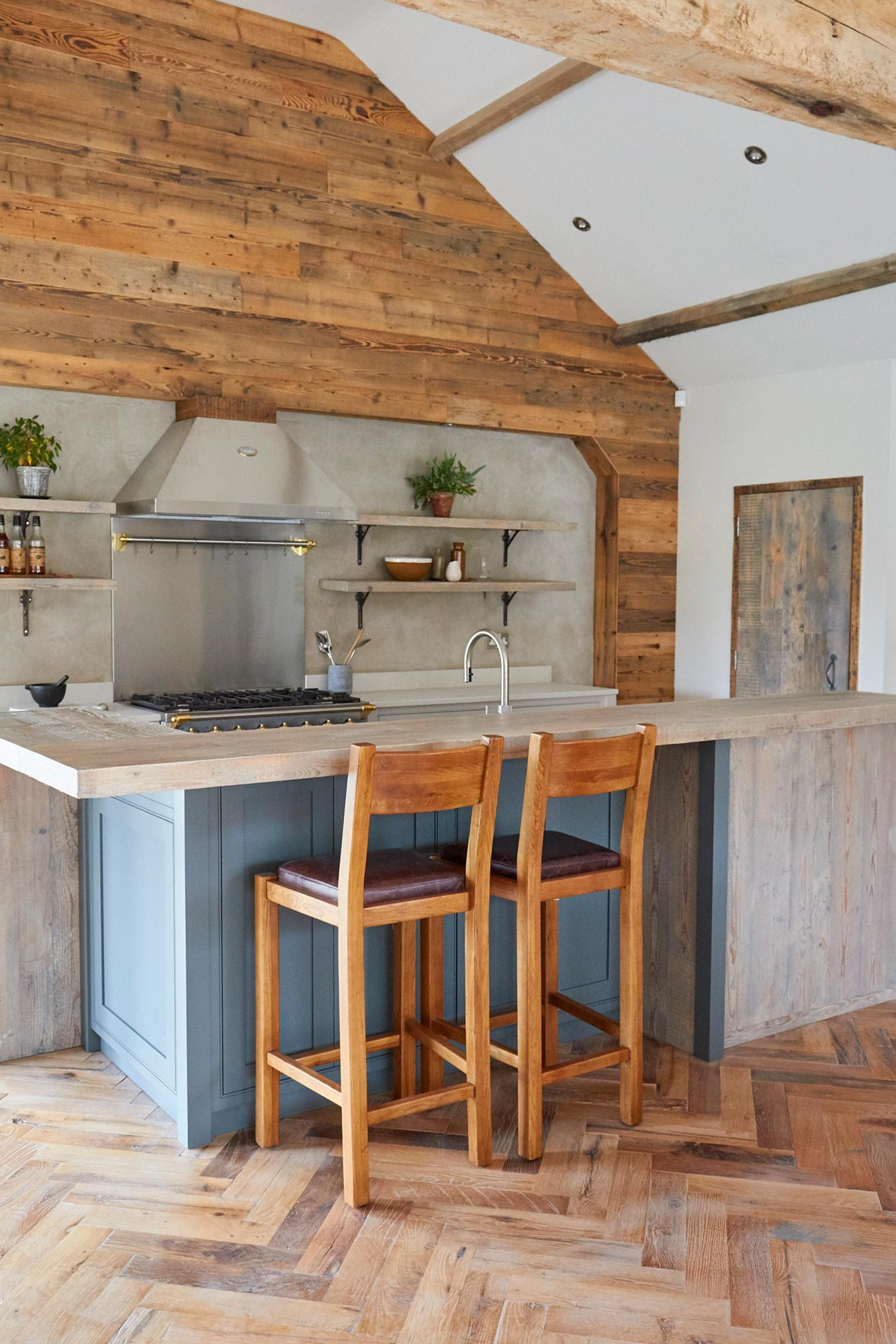 Two oak stools sit under reclaimed pine breakfast bar with painted kitchen cabinets