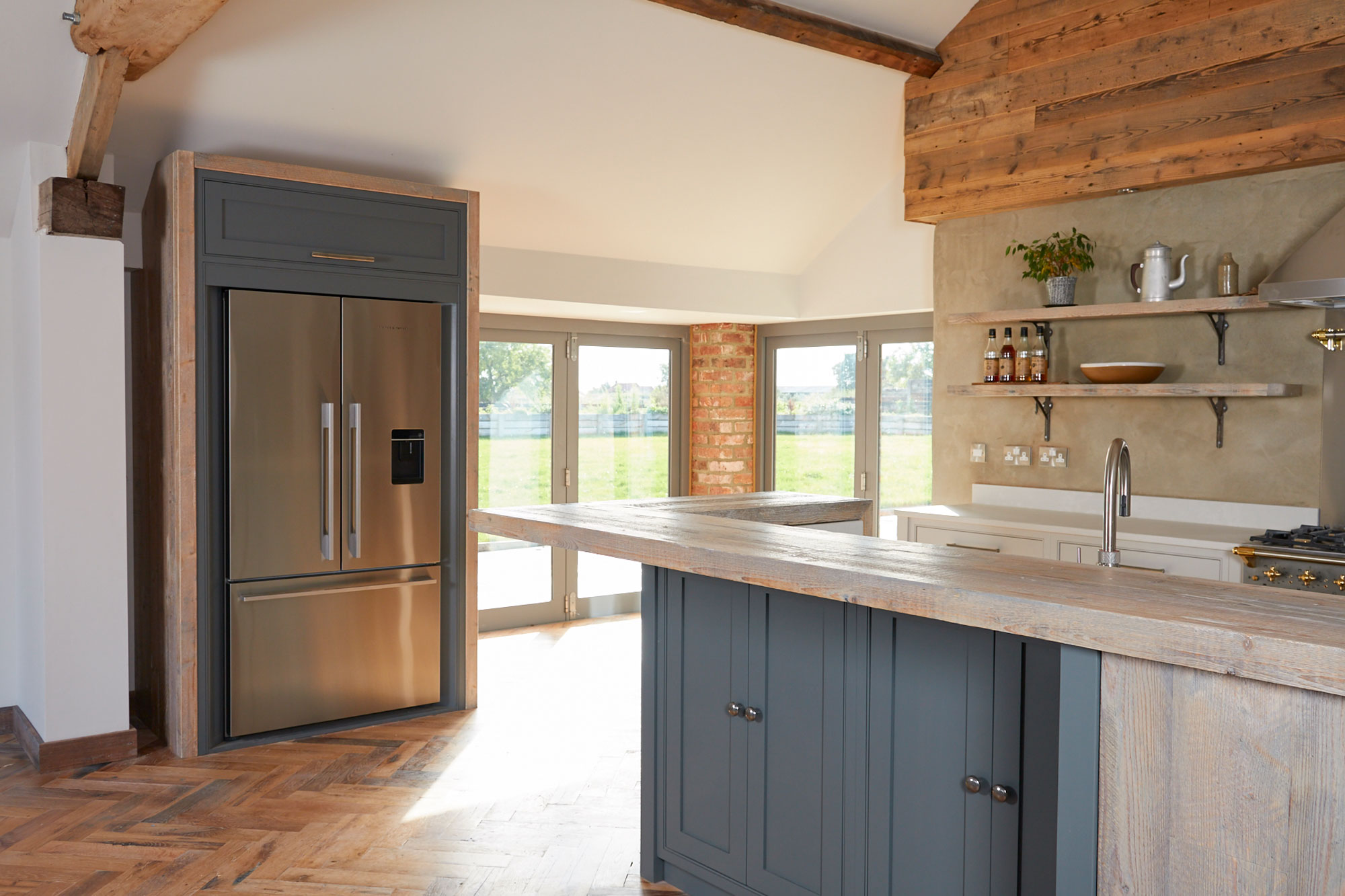 Fisher & Paykel American fridge freezer integrated in to painted unit with rustic oak posts