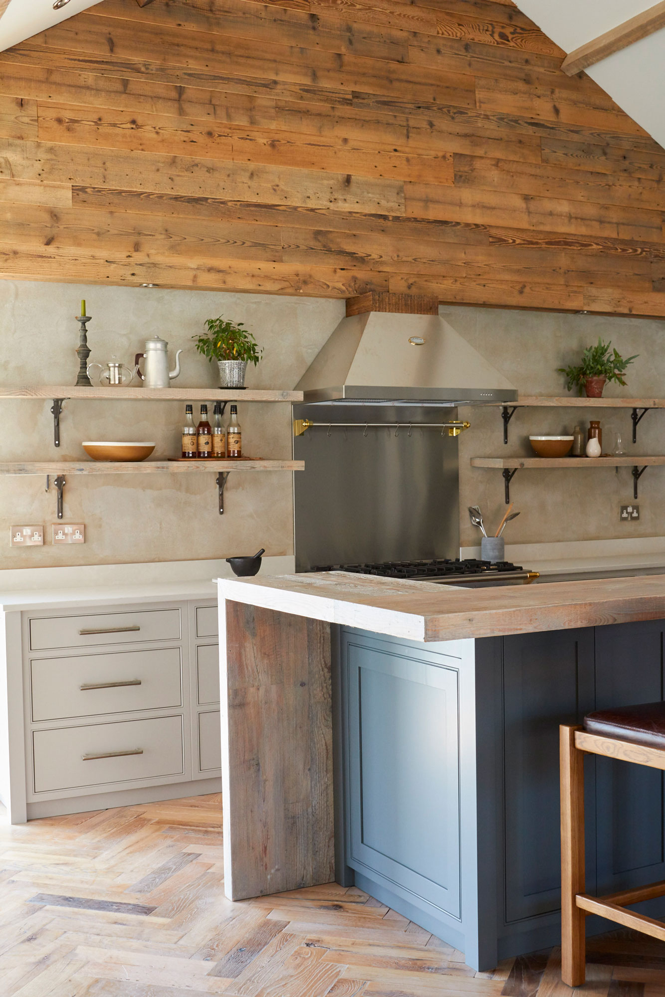 Painted kitchen with herringbone oak floor and cladded reclaimed wood wall
