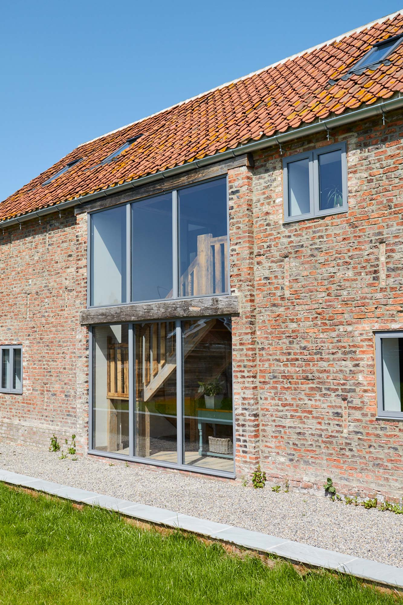 Large glass windows on red brick barn building