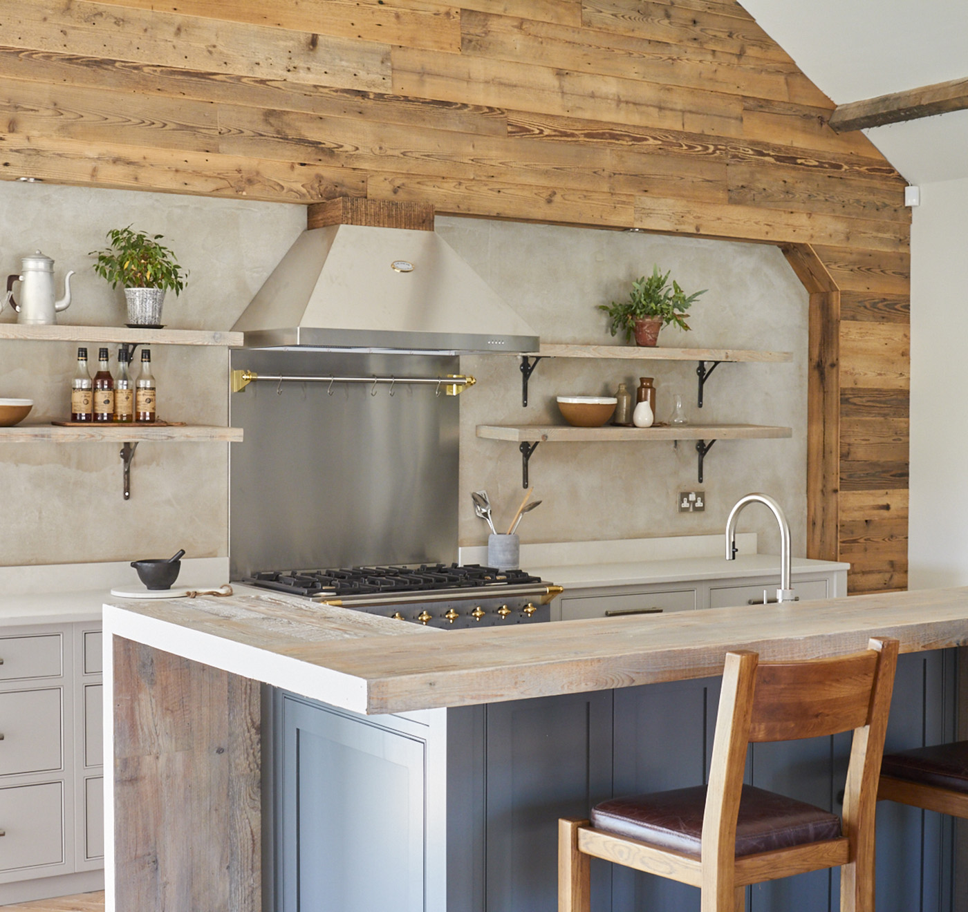 Reclaimed Cladding behind grey island and stainless steel Lacanche range cooker