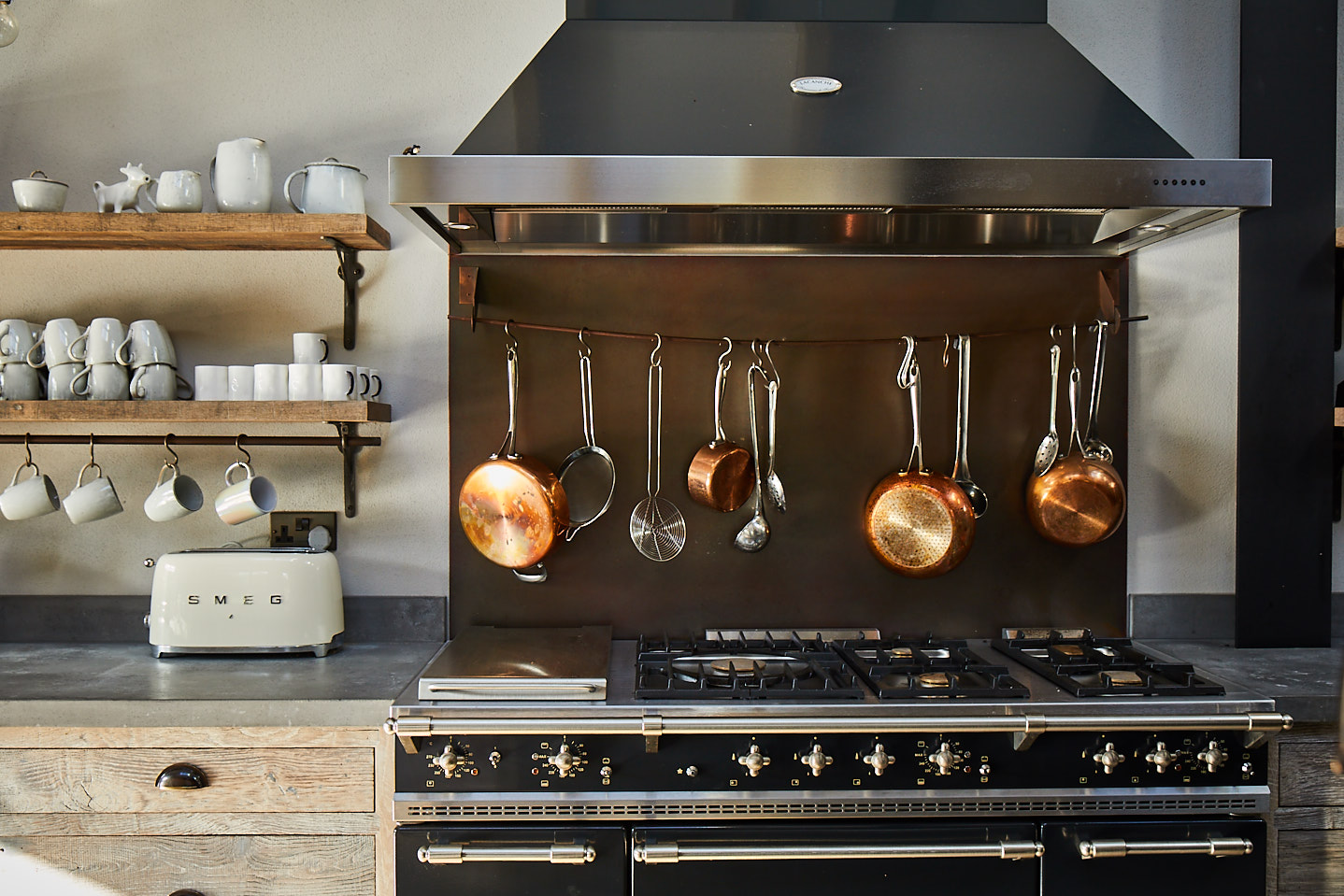 Copper pans hanging above range cooker with large industrial stainless steel extraction