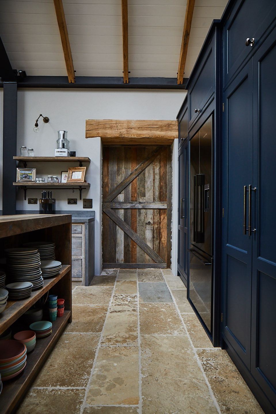 Reclaimed oak sliding barn door next to tall painted dark blue kitchen cabinets