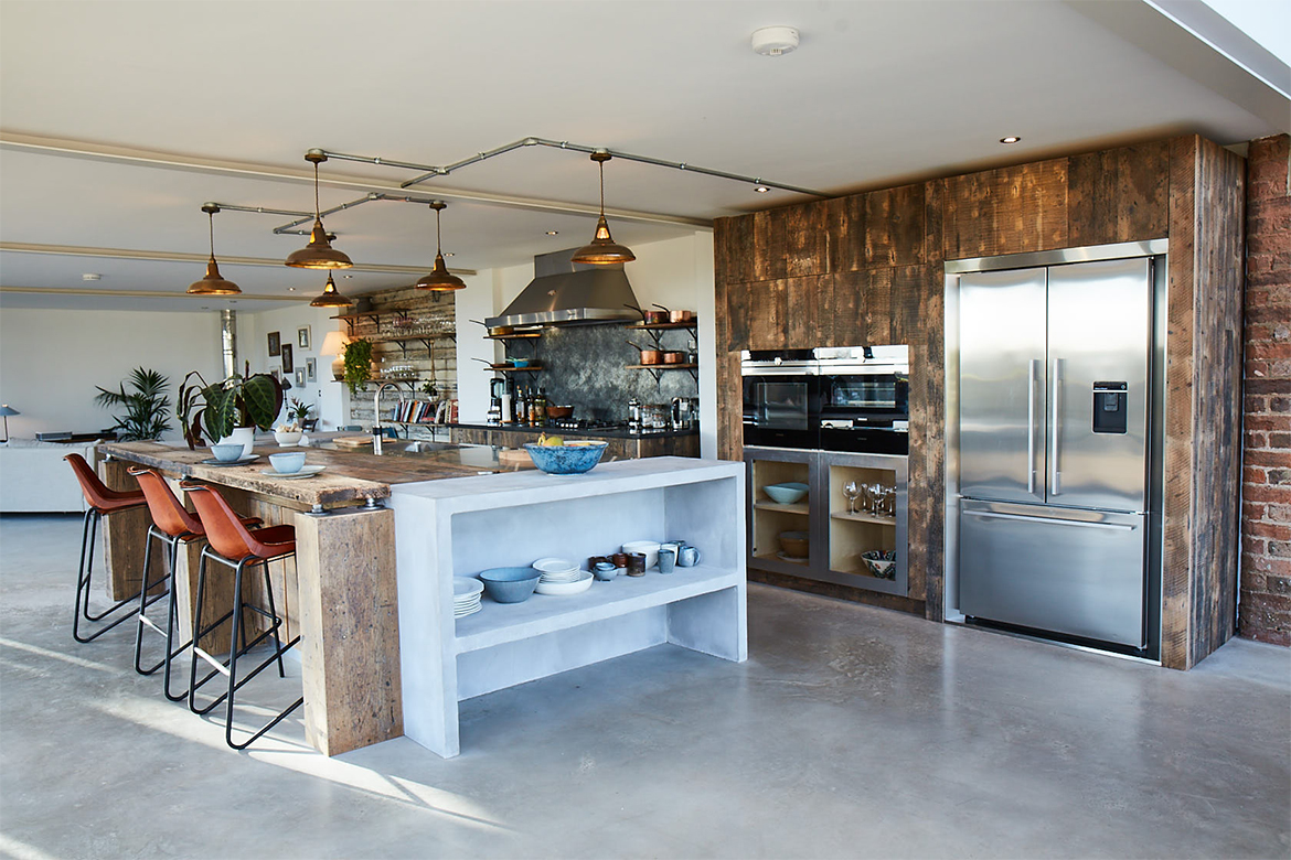 Large bespoke kitchen island with concrete storage and reclaimed oak breakfast bar