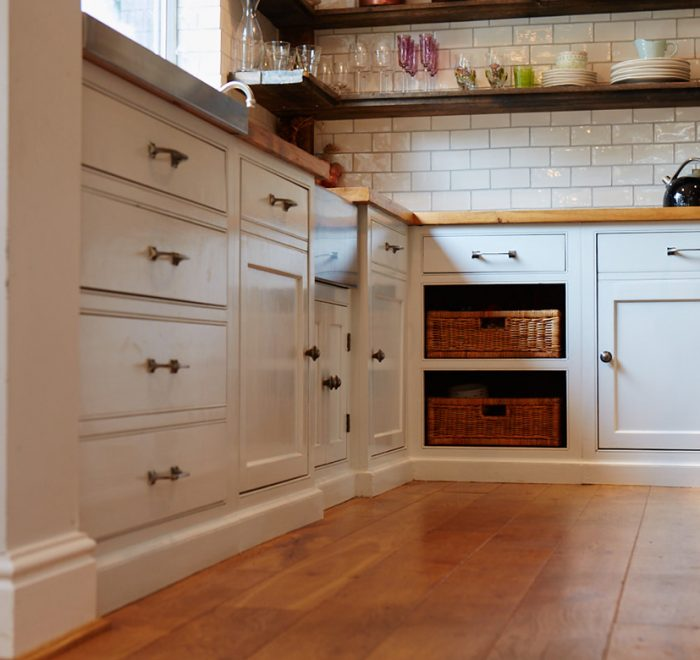 Bespoke kitchen units with reclaimed pine worktop and two exposed wicker baskets
