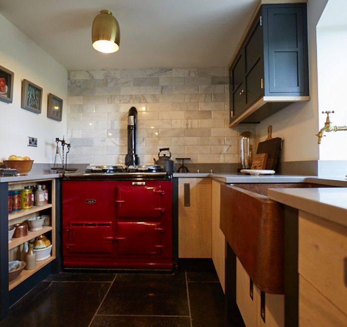 Red AGA sits between bespoke engineered kitchen cabinets and dark painted posts