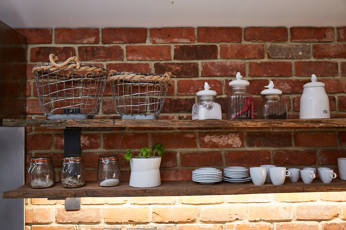 Bespoke reclaimed open oak shelving against an exposed brick wall with various accessories including plates, wirework and vessels
