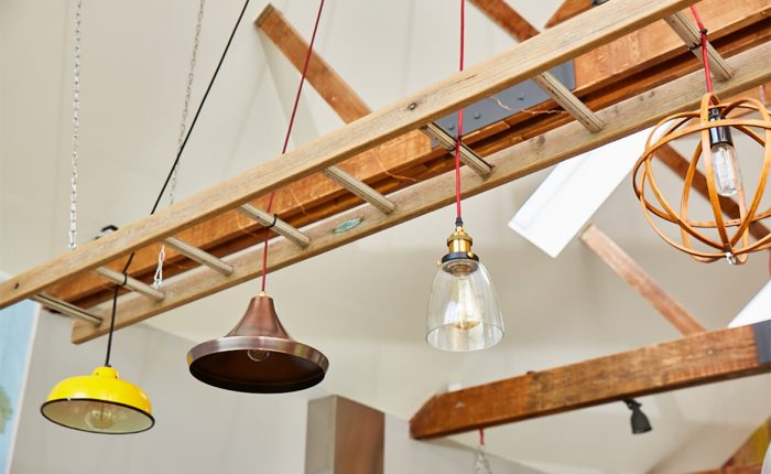Yellow and copper pendant lights hang in between reclaimed ladder