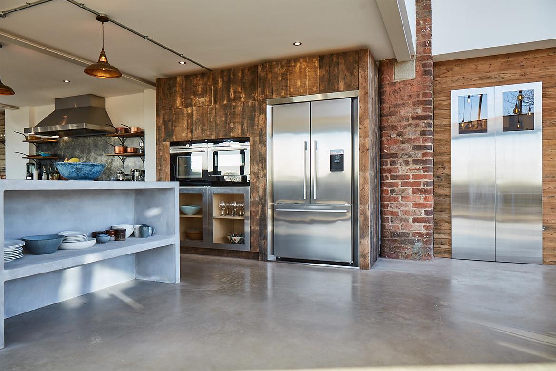 American stainless steel fridge freezer inset in bespoke kitchen units reclaimed from rustic pine oak