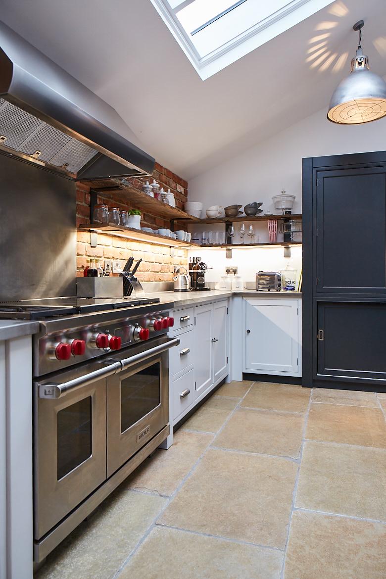 Stainless steel Wolf range cooker with painted bespoke kitchen cabinets by The Main Company