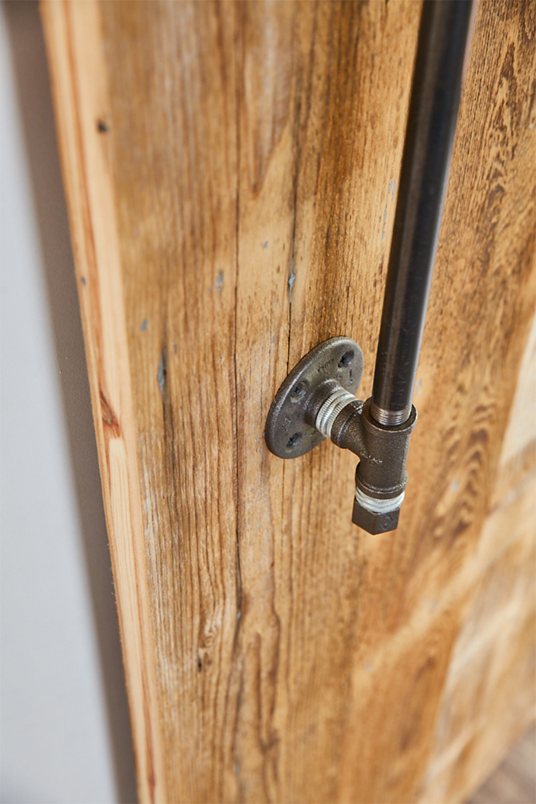Cast iron pipes make handle on reclaimed sliding wood door