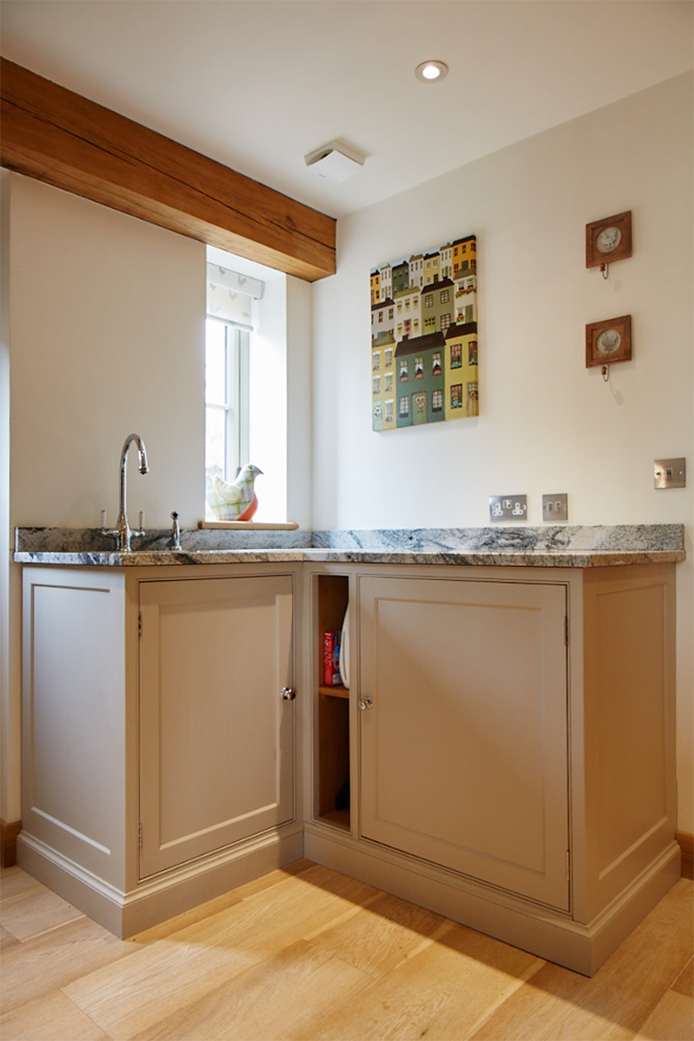 Bespoke painted cabinets allow a small utility 'l' section with inset sink and granite worktops