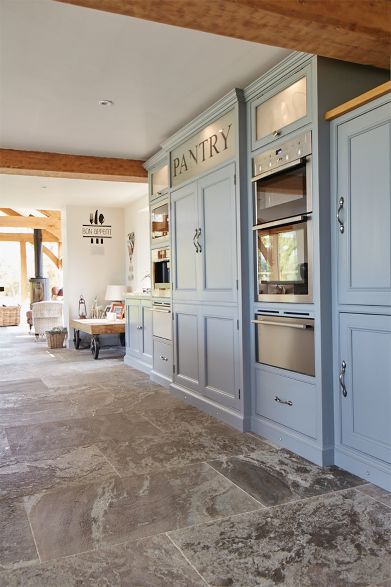 Tall bespoke traditional kitchen light blue units integrating double oven and warming drawer