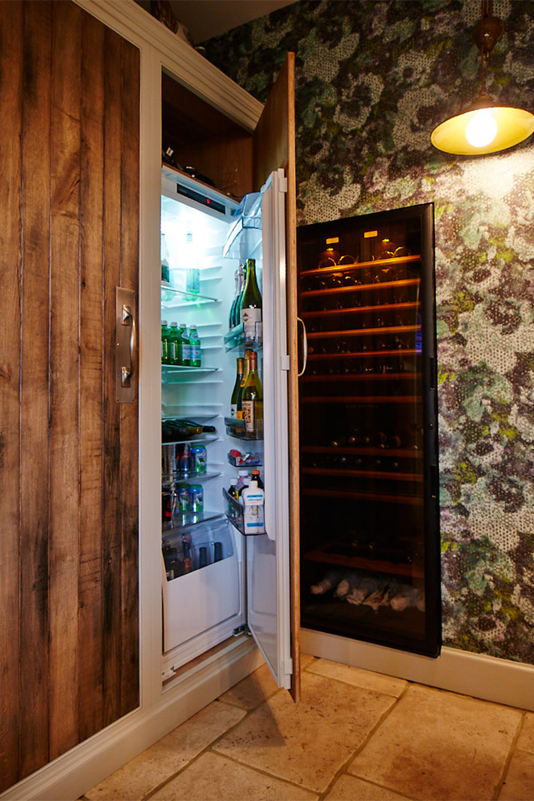 Tall bespoke integrated kitchen beer fridge with solid oak reclaimed rustic door and pewter pull handles
