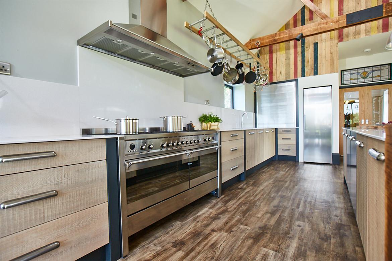 Stainless steel fisher paykel range cooker in between engineered slab oak rustic bespoke kitchen drawers