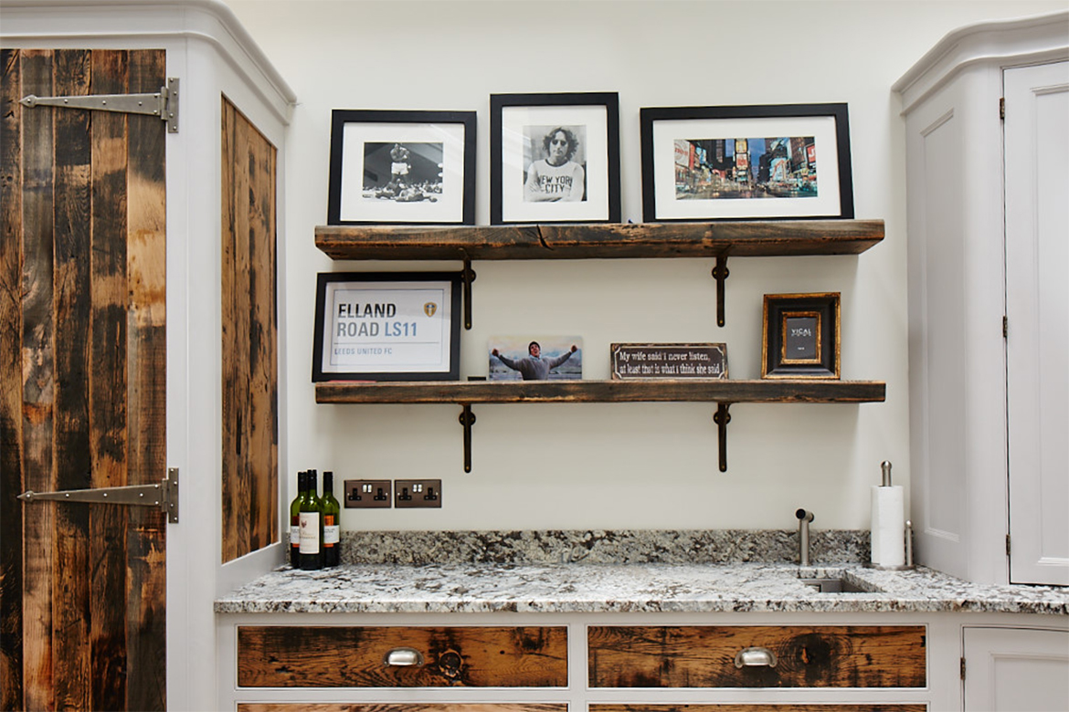 Thick oak reclaimed wood shelves on cast iron brackets with display of photo frames